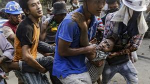 Varios hombres trasladan a un herido en las protestas contra el golpe militar, este domingo en Yangón.