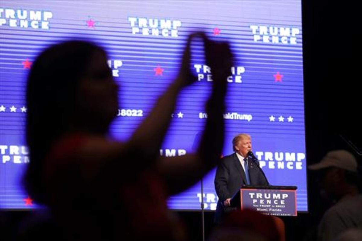 Una electora de Trump se hace una foto para las redes sociales, durante un mitin en Miami.