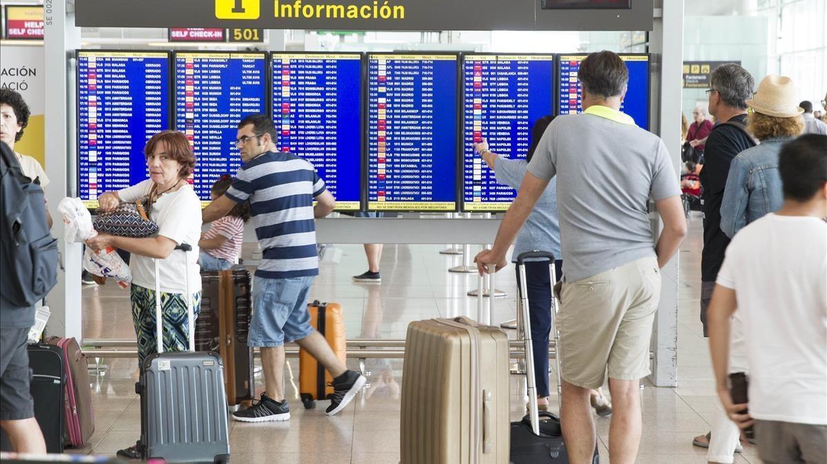 Pasajeros esperando en el aeropuerto de El Prat.