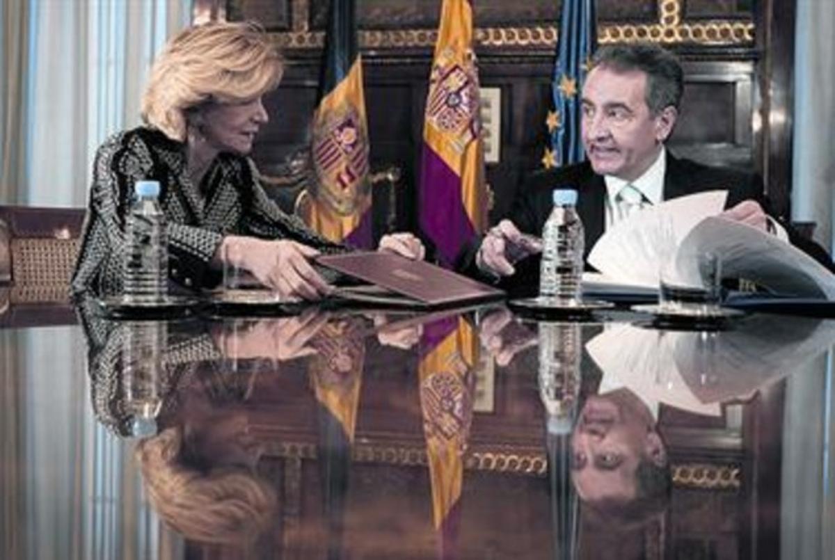 Elena Salgado retira la carpeta del acuerdo, ayer en Madrid, ante la mirada de Bartumeu.