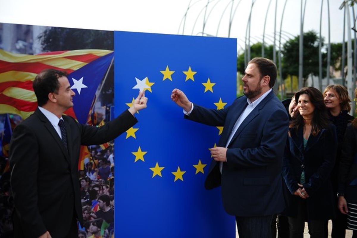 El candidato de ERC, Oriol Junqueras, coloca la supuesta futura estrella del Estado catalán junto al resto de las de la Unión Europea, este jueves, en Barcelona. JORDI COTRINA