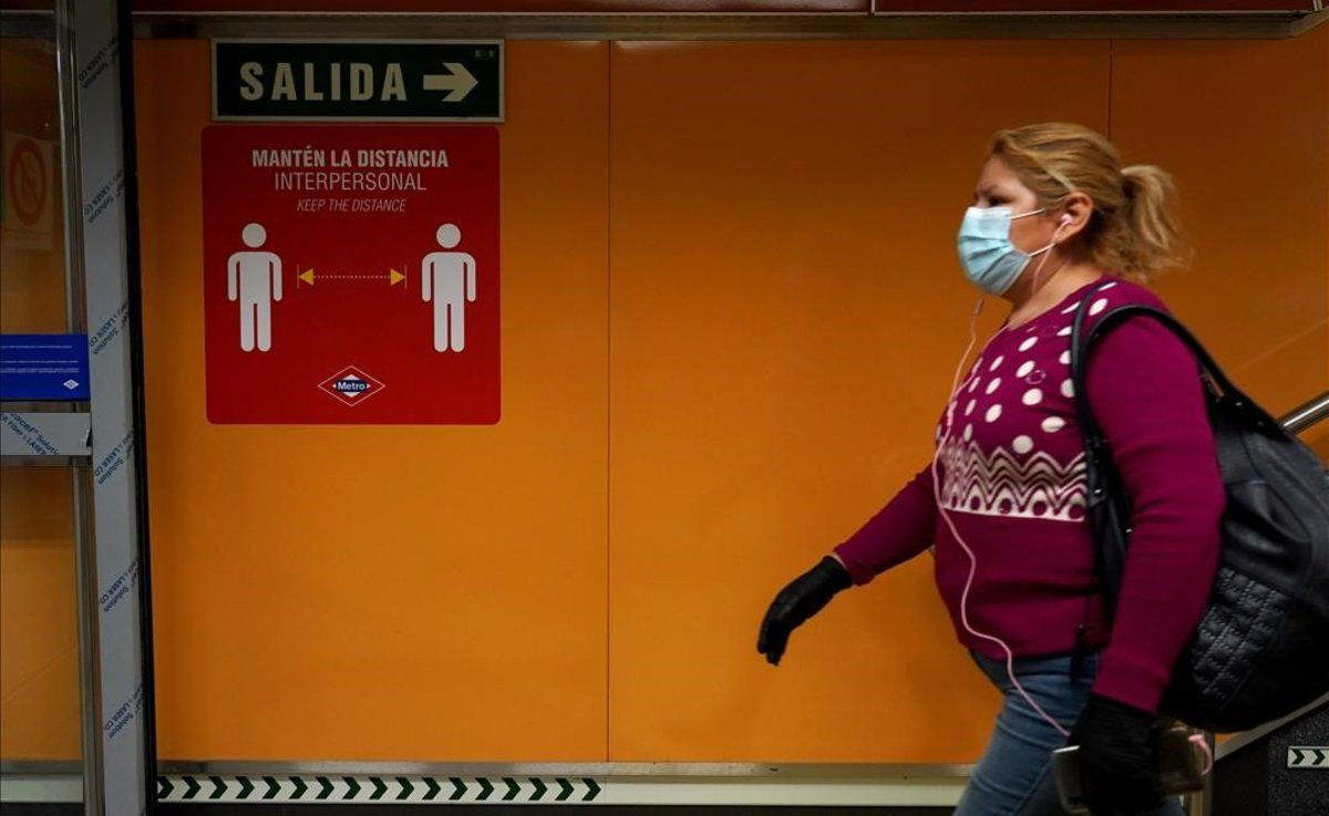 Una mujer en el metro de Madrid, donde pegatinas y carteles advierten de que hay que mantener la distancia interpersonal para evitar el contagio por coronavirus.
