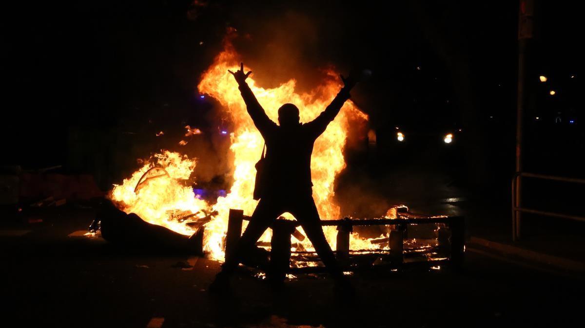 Un manifestante en el centro de Barcelona, frente a un contenedor ardiendo, el miércoles.