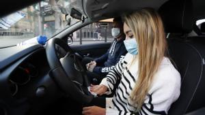 Una chica desinfecta el volante de su coche antes de comenzar la conducción.