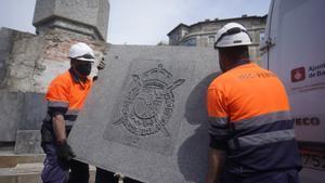 Dos operarios del Ayuntamiento retiran el escudo de Juan Carlos I del obelisco de la plaza Cinc d'Oros.