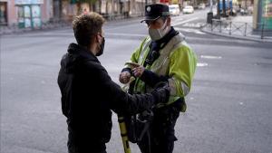 Un policía municipal multa a una persona en patinete eléctrico en un control de acceso a zonas confinadas, en el barrio de Vallecas.