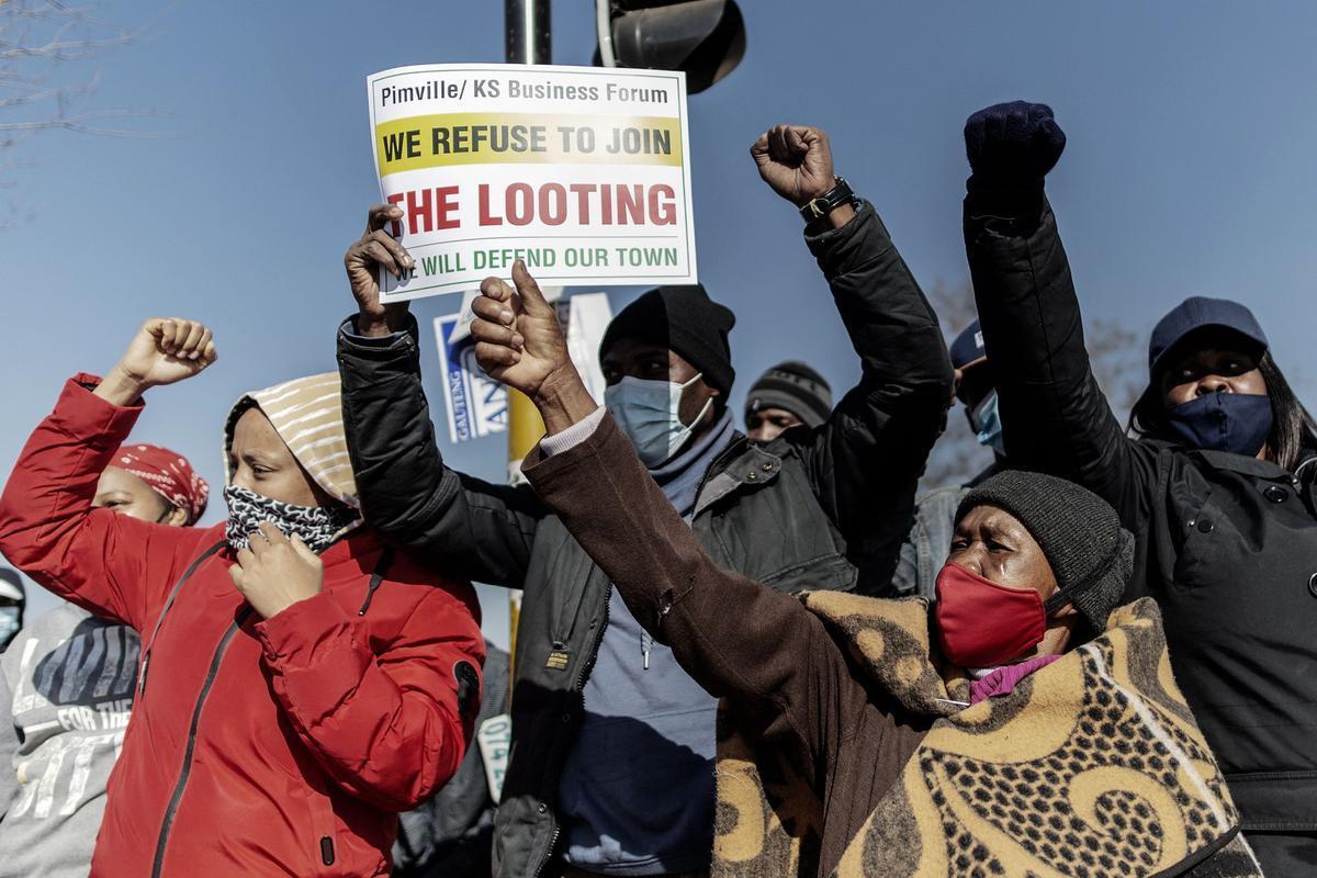 Unos manifestantes con carteles en Sudáfrica.