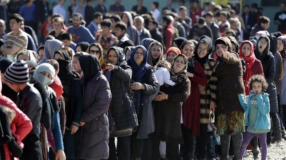 Refugiados afganos reciben comida en Atenas.
