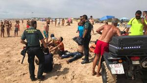 Una patera con inmigrantes llega a la playa de Zahora (Cádiz) ante numerosos bañistas.