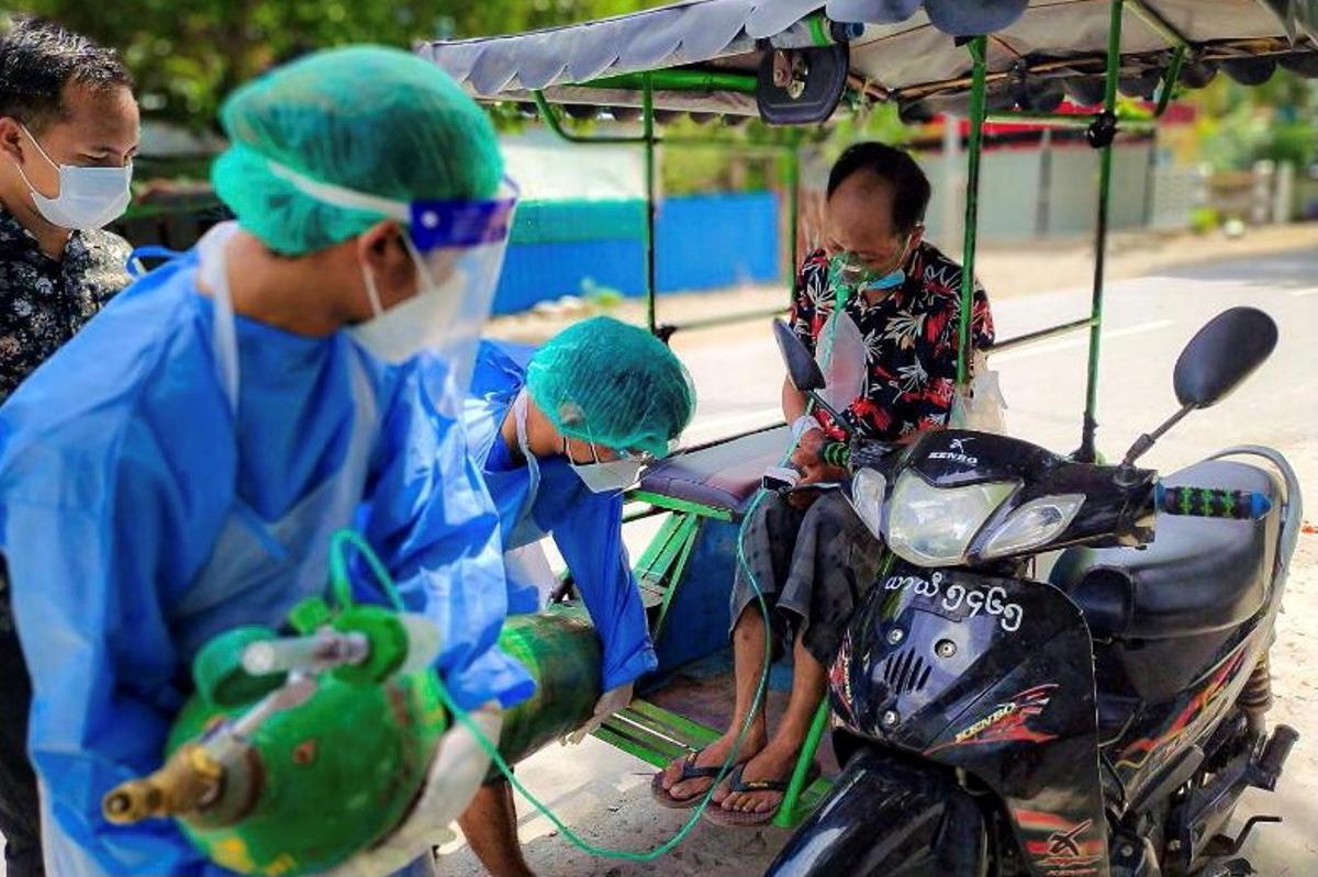 Voluntarios suministran oxígeno a un paciente de covid en la población de Kale, en Birmania.