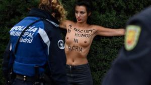 Un agente policial retiene a una activista de Femen, este domingo, en la Plaza de Oriente de Madrid.