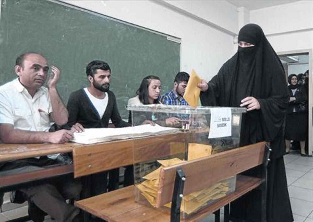 En el colegio electoral 8Una mujer con burka deposita su voto en Estambul, ayer.