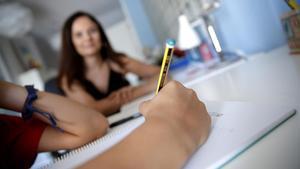 Una madre controla los deberes de su hijo.