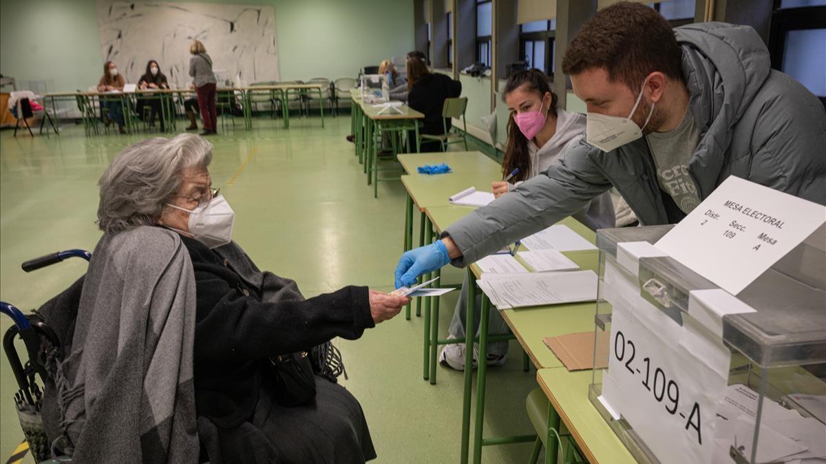 Una señora de 92 anos efectúa su voto en las mesas electorales de la Escola Industrial.