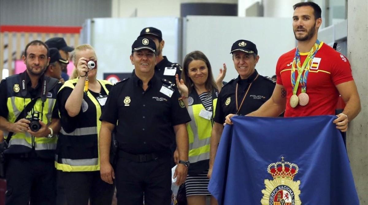 Craviotto, con sus dos medallas y la bandera de la Policía Nacional.