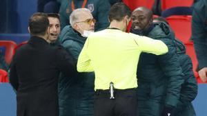 El colegiado Ovidiu Hategan frente a los técnicos del Basaksehir turco, que protestan y fuerzan la salida del campo en el partido de Champions ante el PSG.