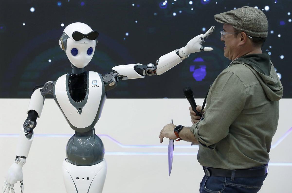 Un robot con tecnología 5G juguetea con uno de las asistentes al Mobile World Congress en Barcelona.