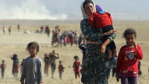 Una mujer yazidí con dos niñas huye del Estado Islámico.