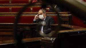 Quim Torra, en el Parlament, visto a través de una barandilla.