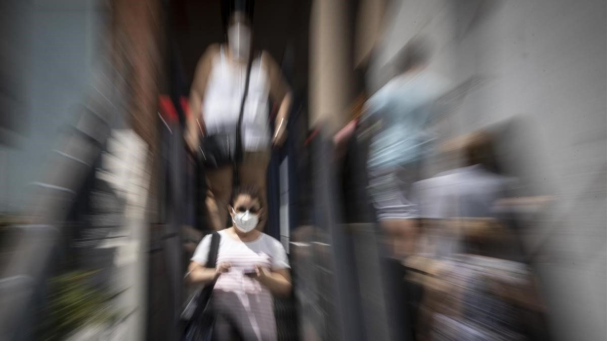 Una persona baja las escaleras del Hospital Vall d'Hebrón cubierta con una mascarilla sanitaria.