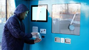 Doctor s assistant Dainis Laugalis scans a saliva test box at a vending machine where people can pick up coronavirus disease (COVID-19) tests and return samples without having to come into contact with others  in Riga  Latvia December 9  2020  Picture taken December 9  2020  REUTERS Janis Laizans