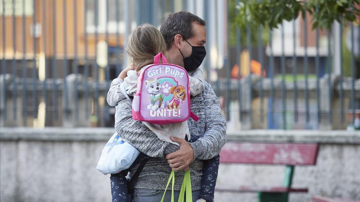 Un padre con mascarilla lleva a su hija en brazos el primer día de colegio el pasado septiembre.