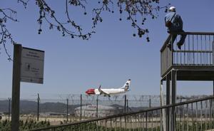 Un hombre observa el aterrizaje de un avión en el aeropuerto desde uno de los miradores del delta del Llobregat.