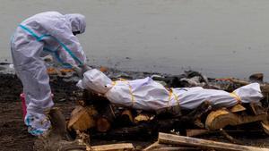 Un hombre con un traje de protección prepara el cuerpo de un familiar fallecido por covid antes de incinerarlo en las orillas del Ganges.