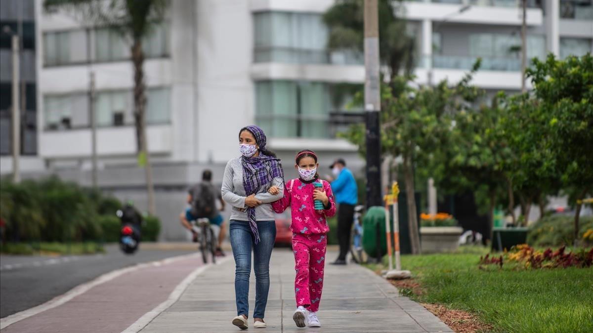 Una mujer y su hija pasean por una calle de Lima,
