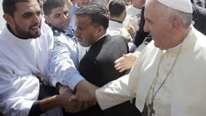 El Papa saluda a un joven sacerdoteantes de una misa en el estadio de Amán (Jordania).