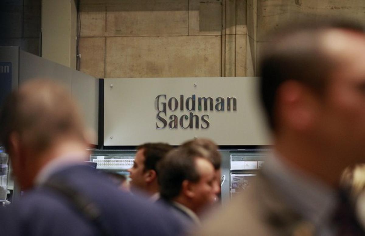 Diversos 'brokers' passen davant el logo de Goldman Sachs a la Borsa de Nova York.