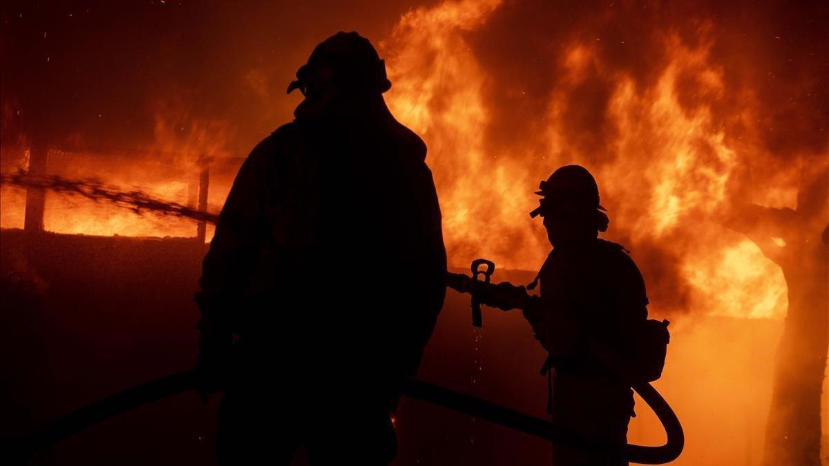 Dos bomberos intentan salvar una casa durante el incedio de Los Ángeles, este lunes.