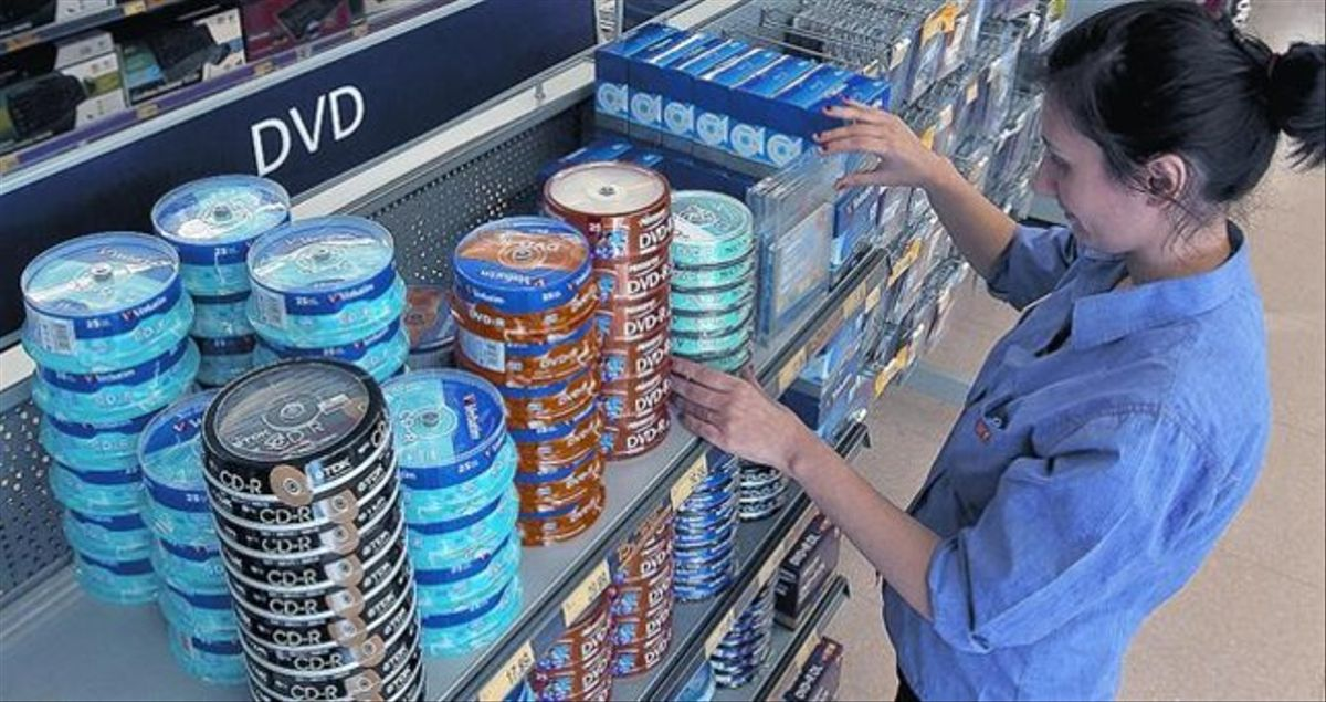 Una empleada de una tienda PC City, en Barcelona, ordena las estanterías de CD vírgenes el pasado marzo.