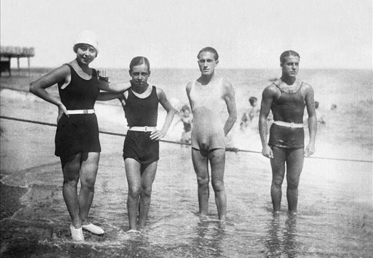 Cuatro bañistas posan en la playa con trajes, al menos en un caso, demasiado ceñido.
