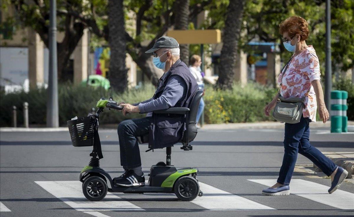 Dos personas mayores pasean por las calles de Valencia en el primer día en que pueden salir a dar una vuelta desde que se decretó el estado de alarma.