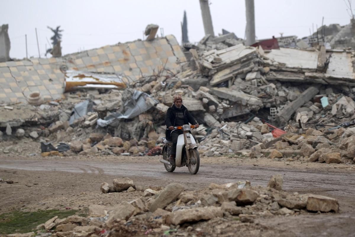 Un hombre circula en moto por los alrededores de Alepo.