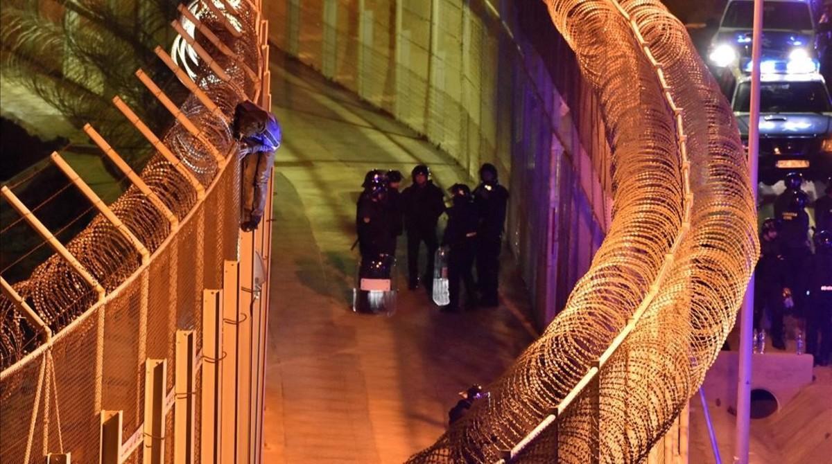 Un imigrante intenta pasarel perímetro fronteriozo de Ceutra entre España y Marruecos.
