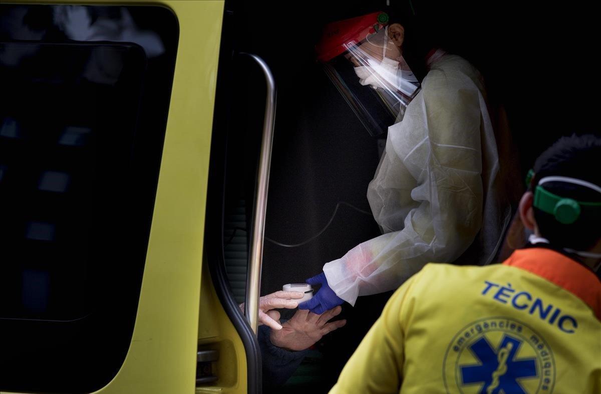 Soledad. El 27 de marzo en Barcelona unasanitaria coloca un pulsioximetro para medir la saturación de oxígeno en sangre en el dedo de un anciano que minutos antes se ha despedido de sus familiares a las puertas de la ambulancia. Su hija le dijo 'hasta pronto' con lágrimas en los ojos al no poder acompañarlo y con la angustia de no saber si lo volvería a ver.