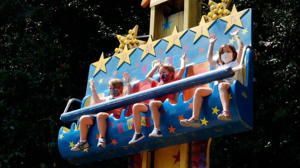 Tres niños con mascarilla disfrutan en una atracción del Tibidabo, el primer dia de su apertura.