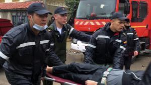 Trabajadores de emergencias evacuan a uno de los heridos en el taller textil clandestino de Tánger inundado por las fuertes lluvias, este lunes.