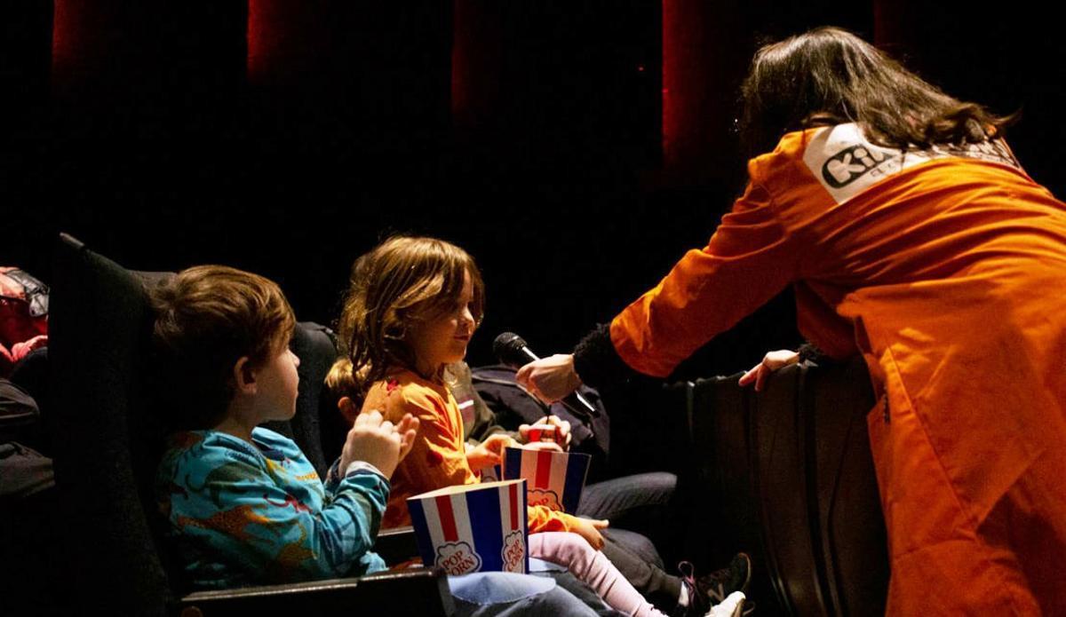 Una animadora habla con una niña durante una sesión de Kinosaure.