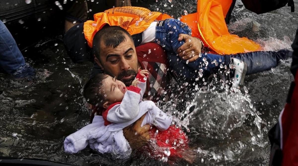 Un refugiado intenta mantener fuera del agua a su hijo para que no se ahogue frente a las costasde Lesbos.