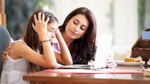 Una madre escucha a su hija delante de un ordenador.