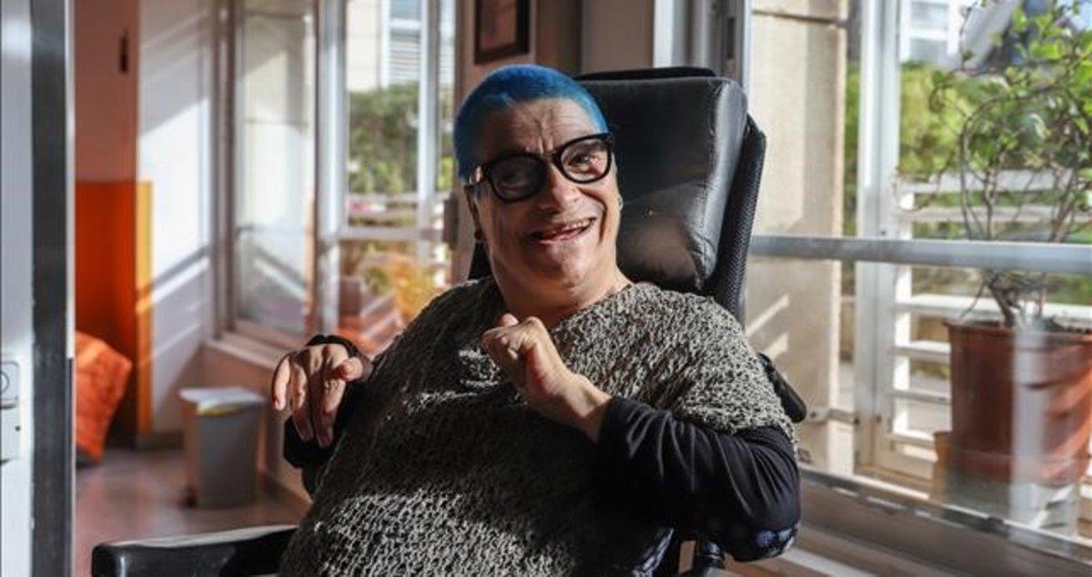 Feliz y con una sonrisa en su rostro posa en el salón de su casa To Monreal, una mujer con parálisis cerebral