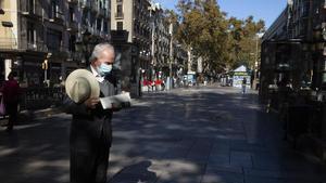 Un hombre lee el diario en una Rambla prácticamente vacía, el pasado miércoles.