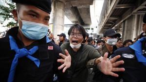 La policía detiene a uno de los participantes en la marcha de protestas en Bangkok.