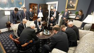 Mike Pence (sentado en una silla en primer plano, de espaldas) reza junto a su equipo de trabajo en la Casa Blanca, el pasado día 26.
