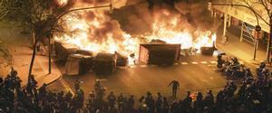 Contenedores ardiendo en la confluencia de las calles Aragó y Bailén de Barcelona en el tercer día de protestas por el encarcelamiento de Pablo Hasél.