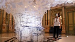 Una mujer observa la instalación 'Last hope', de Chiharu Shiota, en el Saló dels Miralls del Liceu, este lunes.