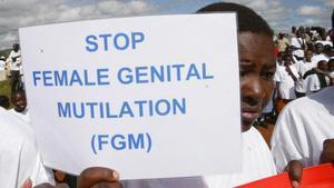 Una mujer sostiene una cartel contra la Mutilación Genital Femenina en una protesta enKenia.
